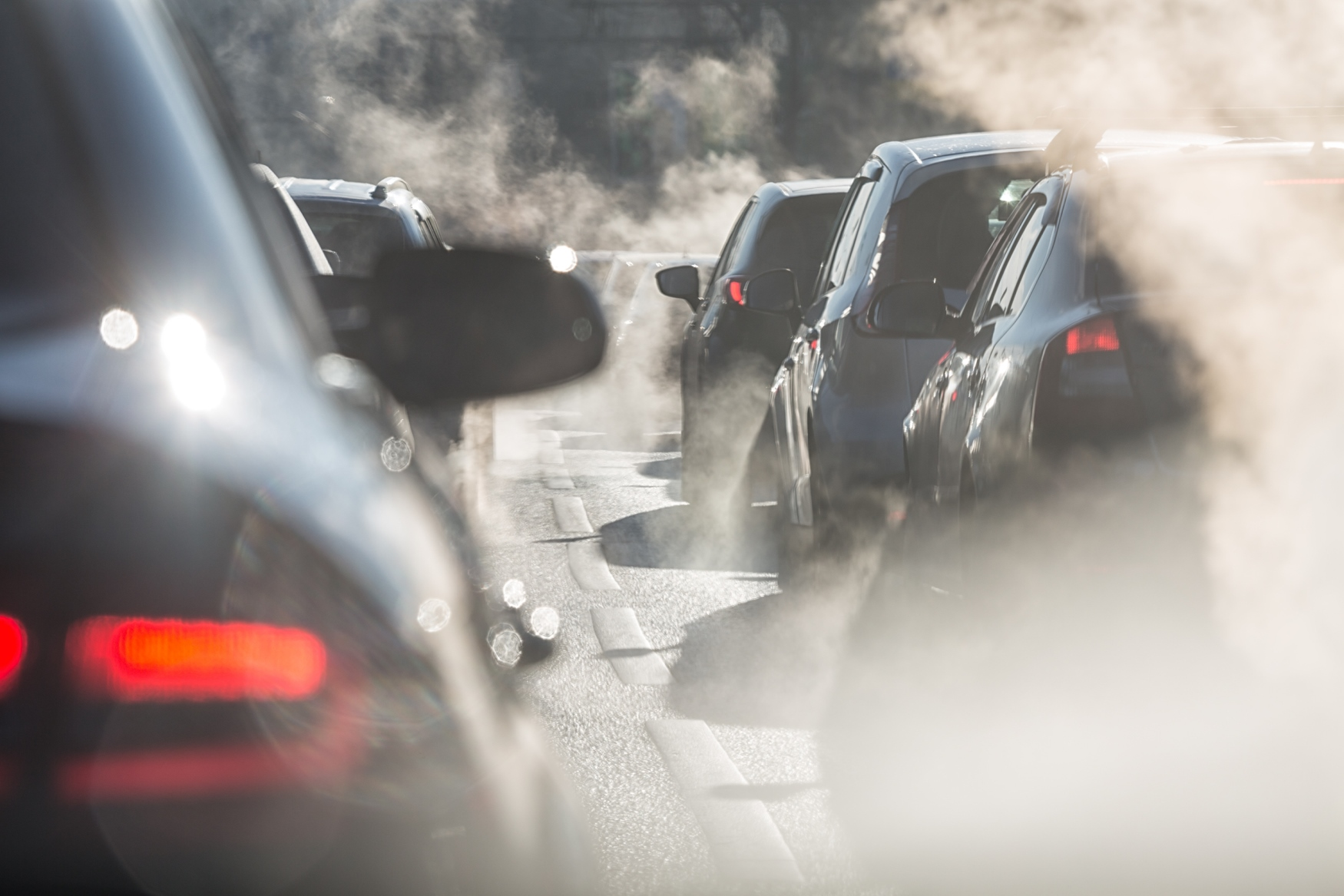 Photo of cars in traffic emitting exhaust fumes