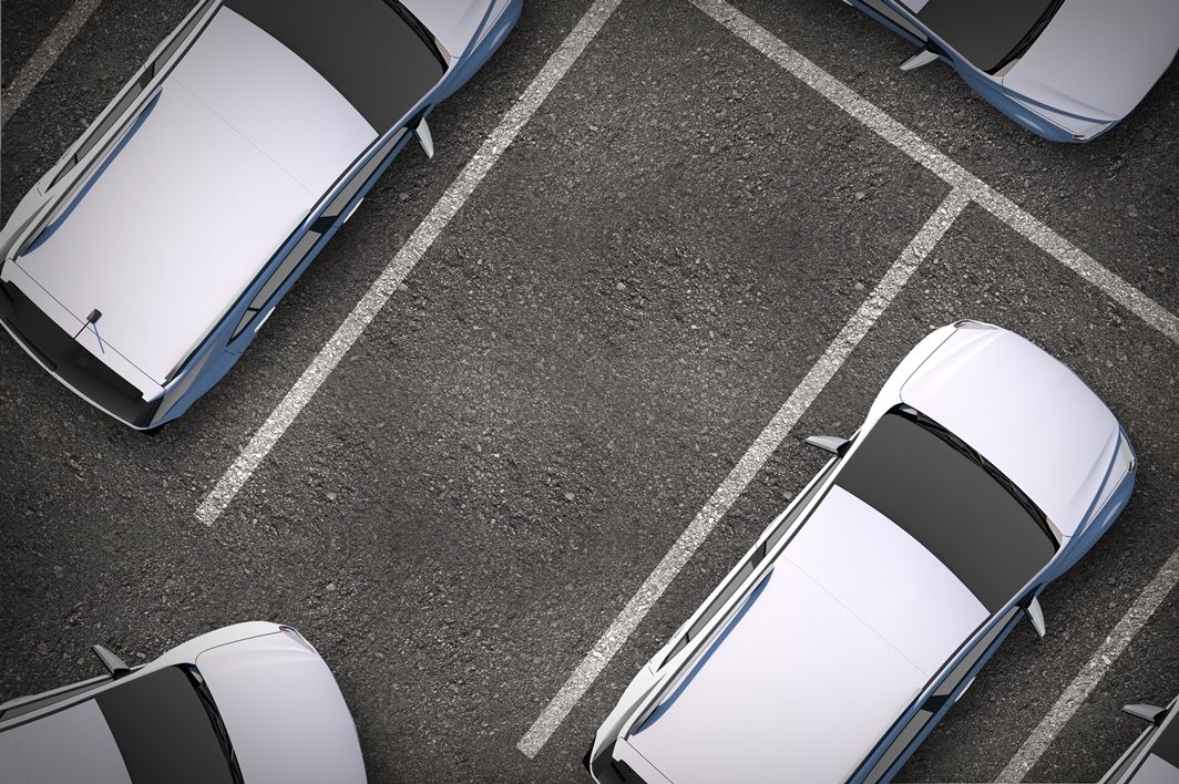 Photo of cars in a car park, with a car entering a space