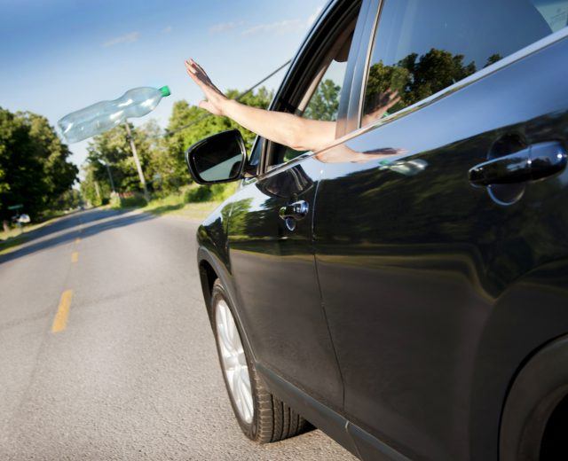 Photo of person throwing litter out of a moving car