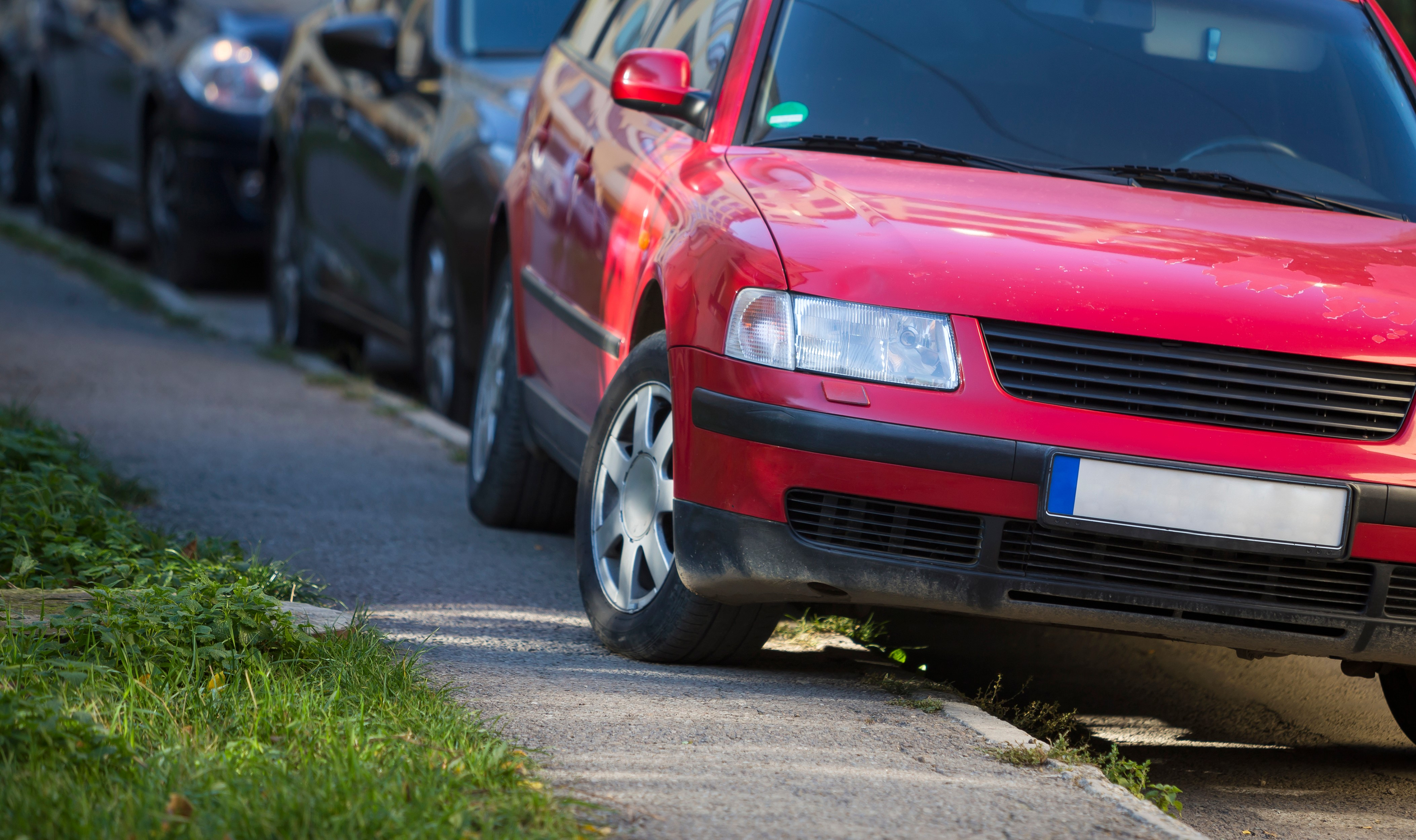 Photo of a car red car parked on the pavement