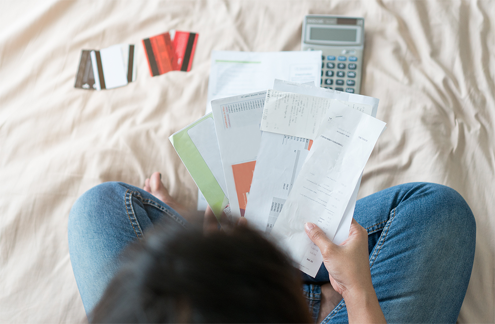Photograph of person with letters owing debt sitting in front of a calculator